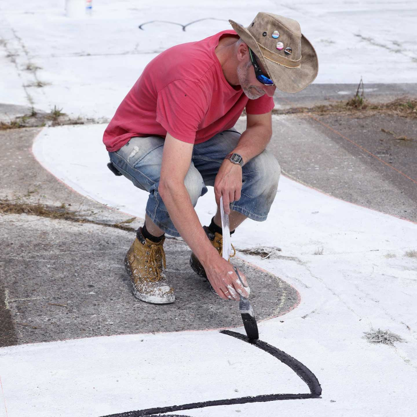 artist painting on the runway at Waterbeach